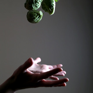 two hands tossing up brussels sprouts