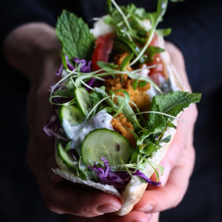 Two hands holding a pita stuffed with red lentil fritters