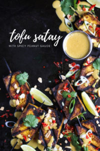 Tofu Satay on a black background, with spicy peanut sauce and herbs