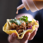Close up shot of a handheld taco, with a squeeze bottle of sauce