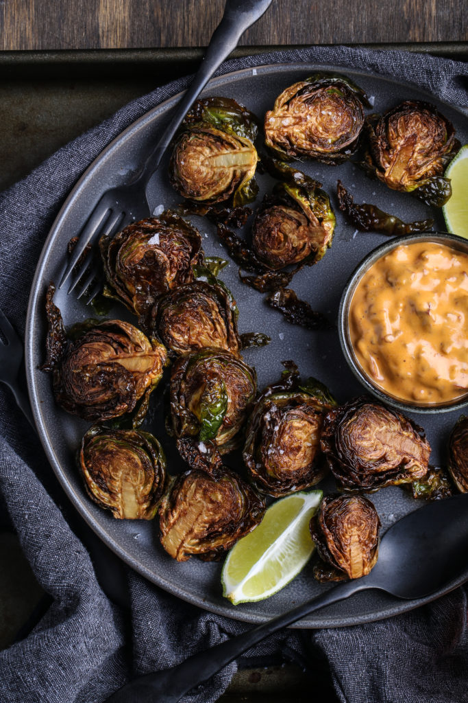 A plate of deep-fried Brussels sprouts, with orange sauce, on a plate