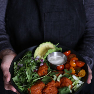 Person in Apron, holding a buffalo cauliflower salad