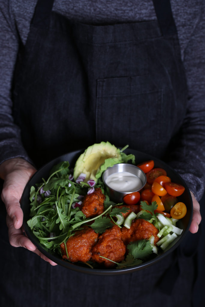 A person wearing an apron, holding a buffalo cauliflower salad
