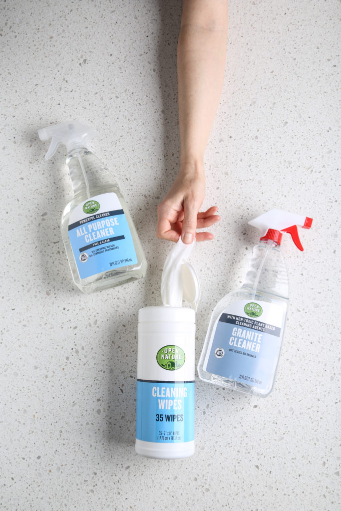Open Nature Cleaning Products, one hand pulling cleaning wipe from container