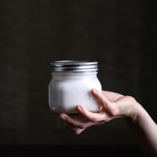 Hand holding a jar of coconut yogurt