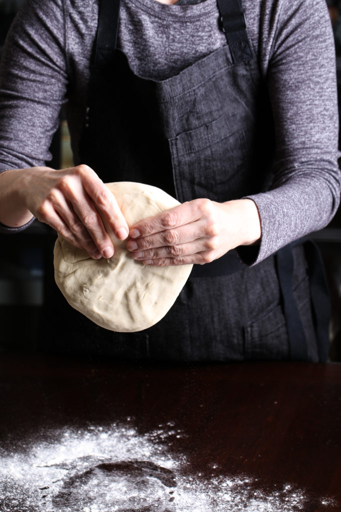 hands forming pizza dough