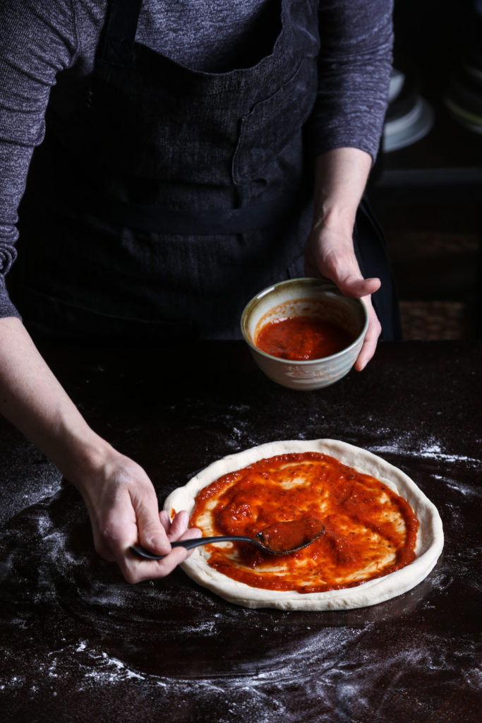 hands smearing pizza sauce over pizza dough