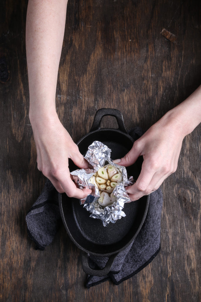 two hands wrapping a head of garlic in foil