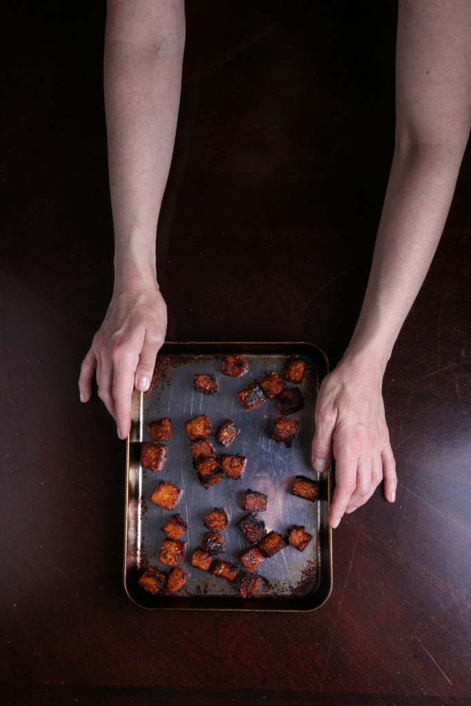 two hands holding a tray of baked smoky tempeh cubes