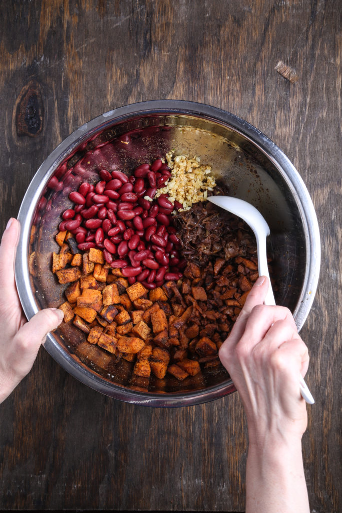 A top-down shot of a prep bowl with two hands mixing up ingredients