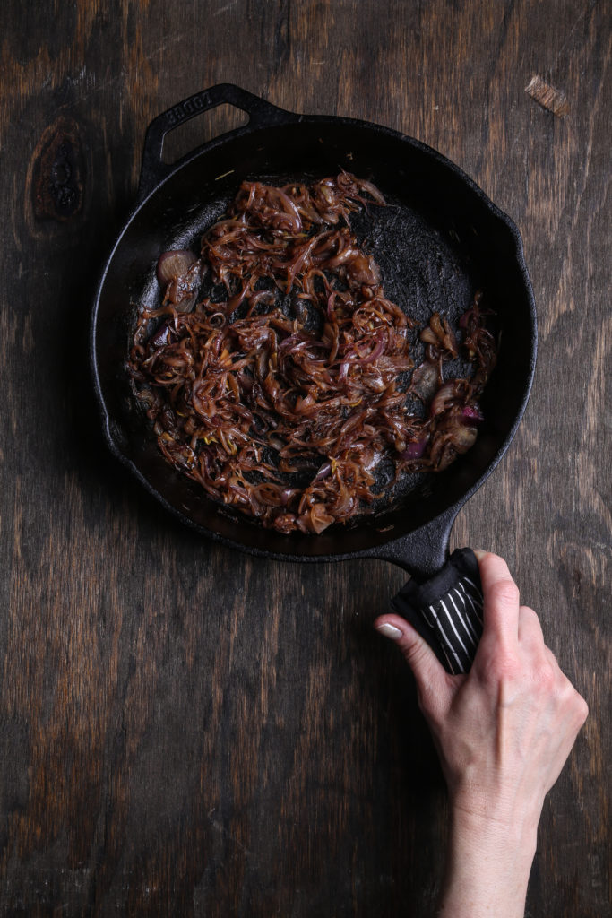 a top-down shot of caramelized onion in a cast iron pan