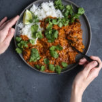 Two hands with a plate of curry and rice, on a dark background