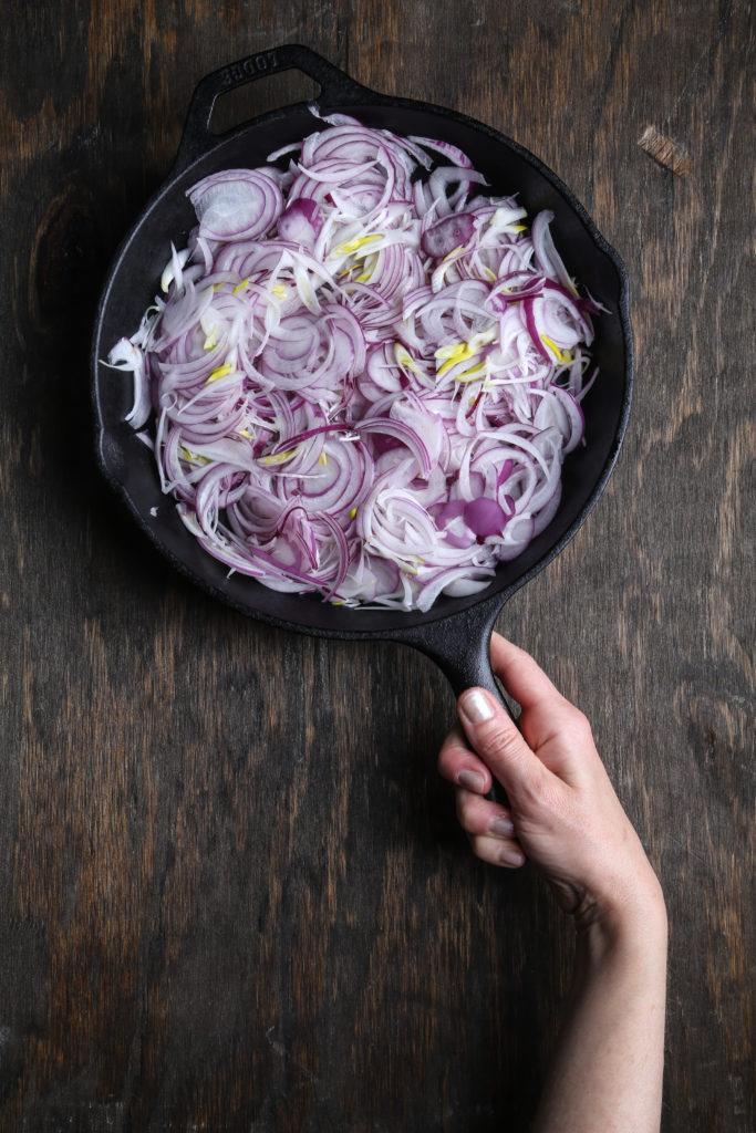 mandolined red onion in a cast iron pan
