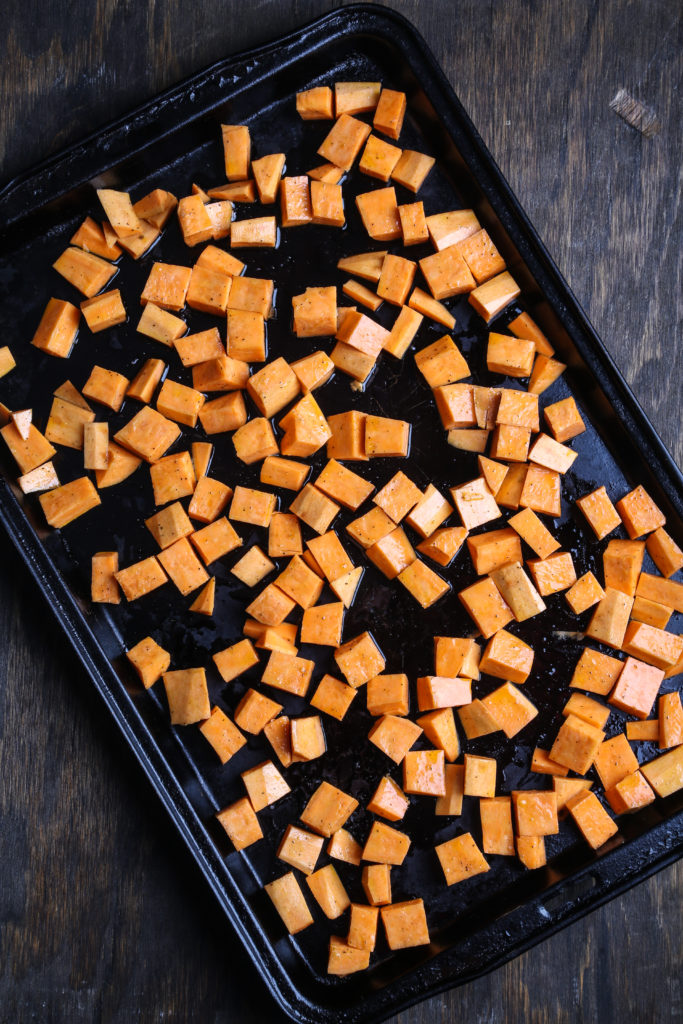 a top-down shot of cubed sweet potato on a baking sheet