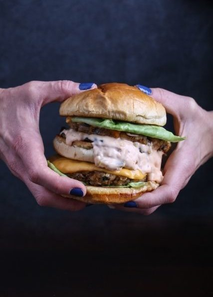 two hands holding a double-decker burger