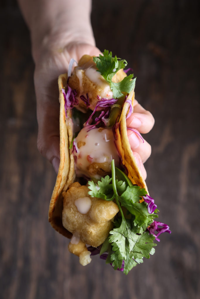 One hand holding a cauliflower taco