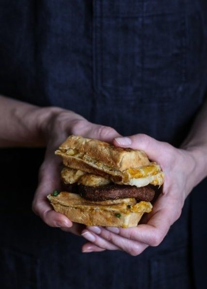 Two Hands Holding a Vegan Sausage Wafflewich
