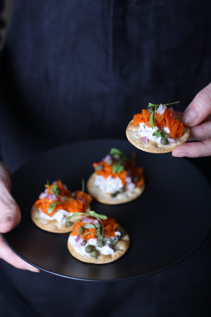Two hands holding a plate of carrot lox crackers app