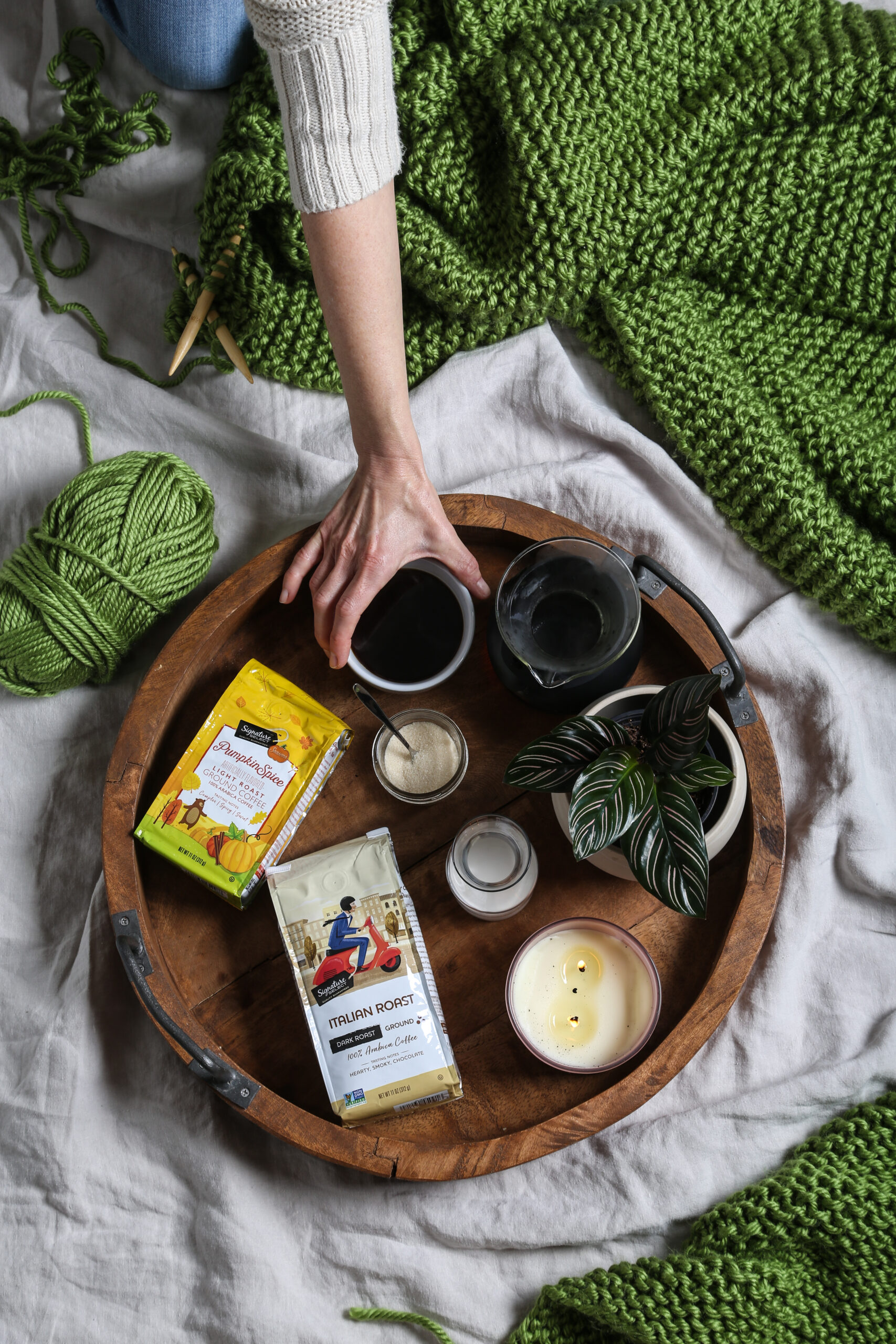 a top-down shot of a knitted blanket and coffee