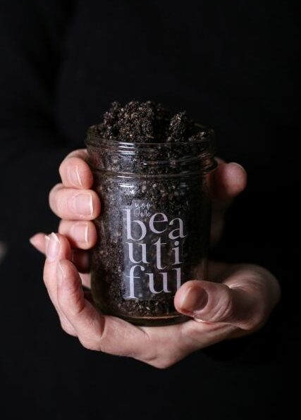 two hands holding a jar of homemade coffee sugar scrub