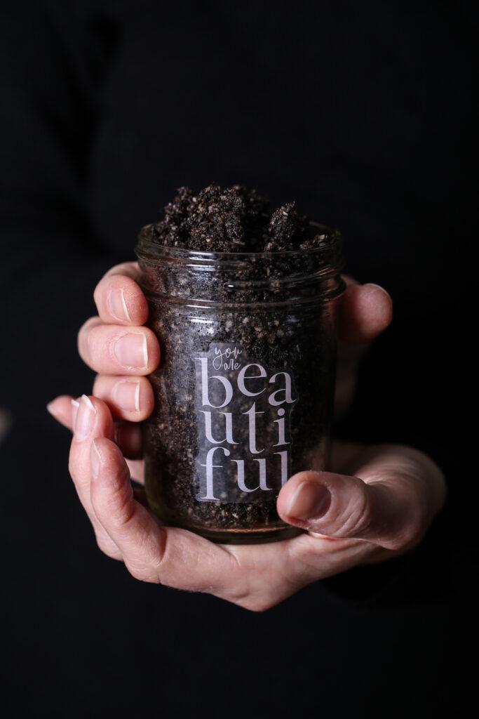 Two hands holding a glass mason jar of coffee sugar scrub