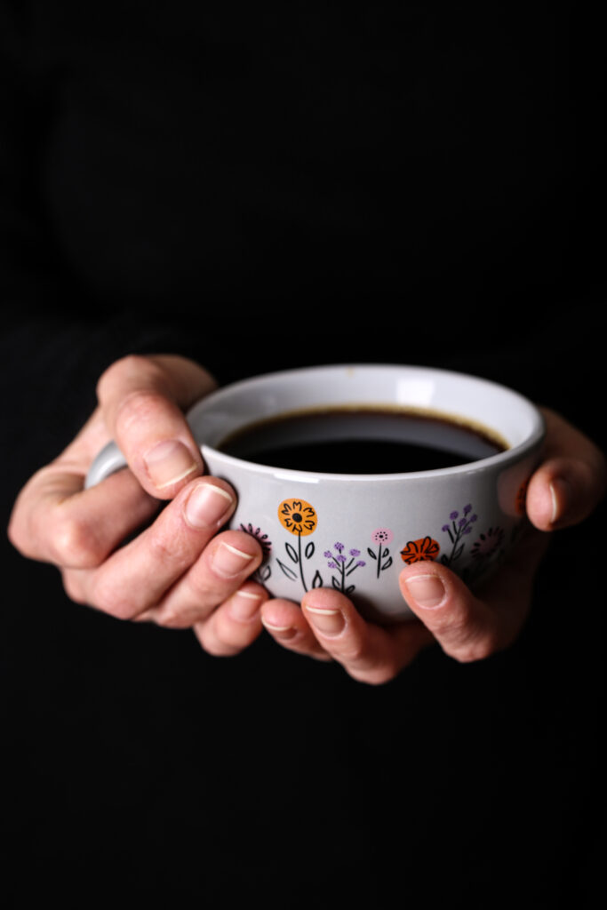 two hands holding a cup of coffee
