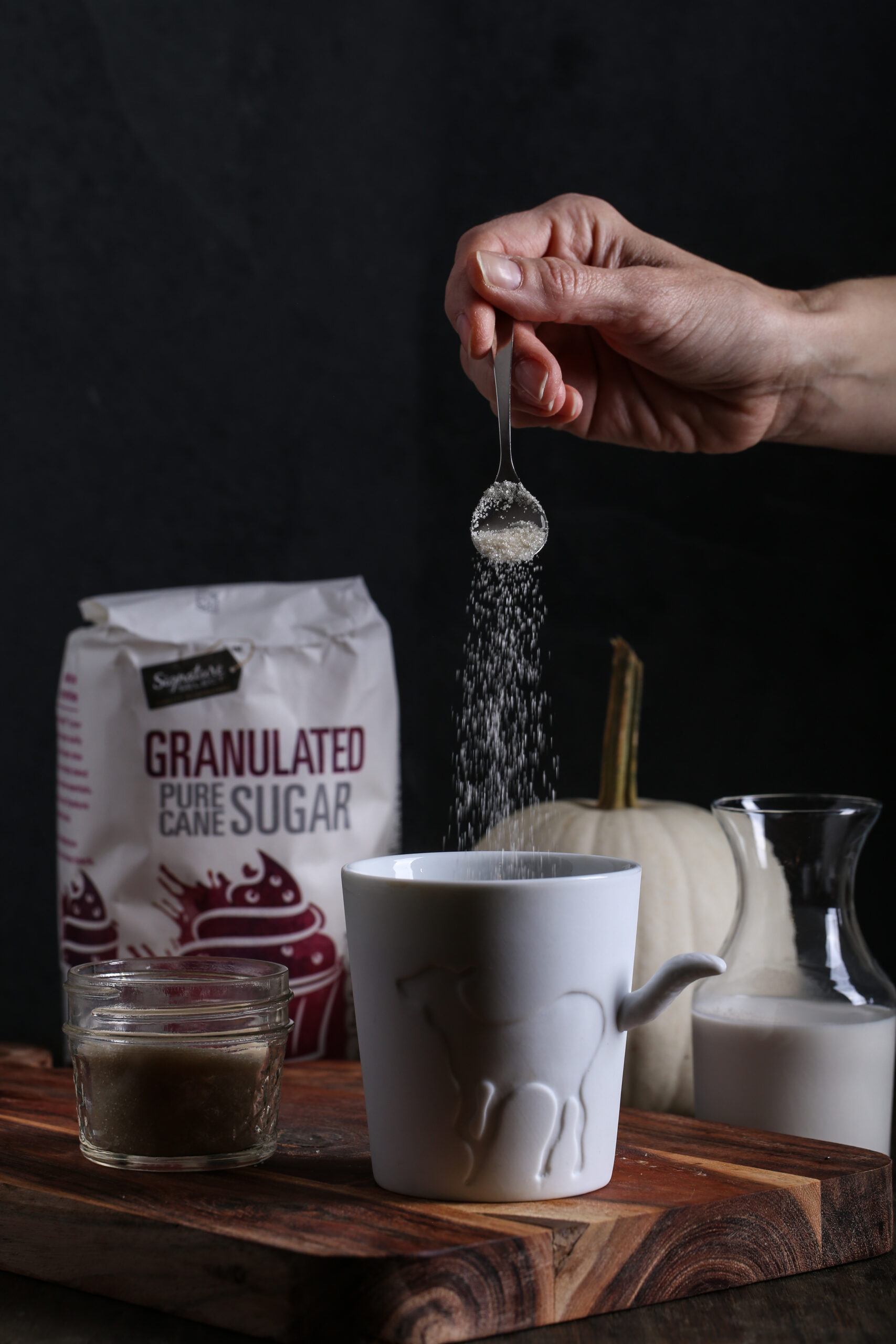 Sugar being added to a cup of coffee
