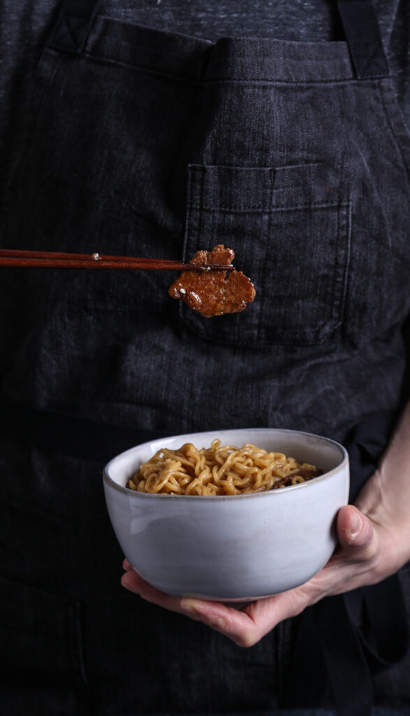 two hands holding a bowl of vegan ramen, with a piece of seared seitan